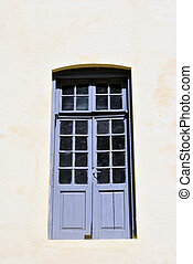 French door hanging on the wall of old building in wood and...