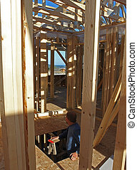 second story of unfinished house - a man looking through the...
