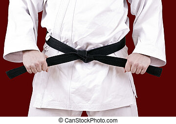 black belt - Martial arts athlete tying the knot to his...