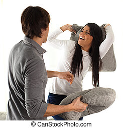 couple fighting with pillows on white background