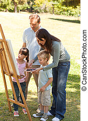 Family painting together in the par