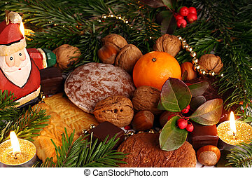 Sweets under the cristmas tree. - Candles and sweets under...