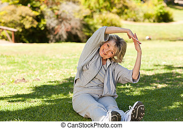Senior woman doing her streches in the park