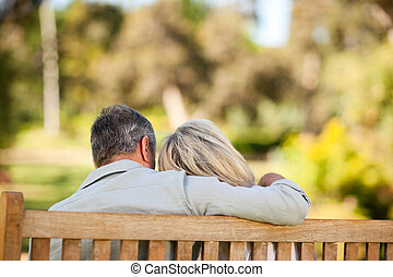 Elderly couple sitting on the bench with their back to the...