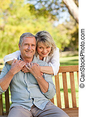 Senior woman hugging her husband who is on the bench