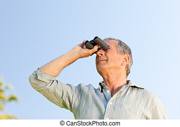 Man looking at the sky with his binoculars