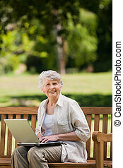 Mature woman working on her laptop on the bench