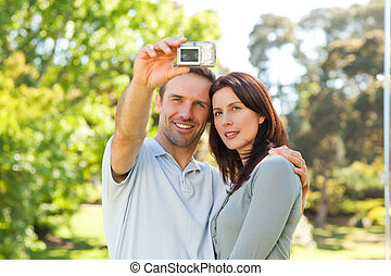 Couple taking a photo of themselves in the park