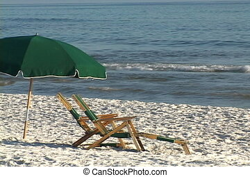 Beach Seats - Two vacant beach chairs sit in the sand under...