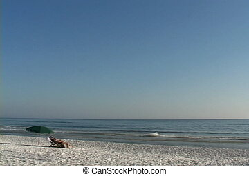 Beach Vacationers - Two tourists relax in beach chairs on an...