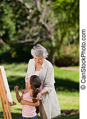 Grandmother and her granddaughter painting in the garden