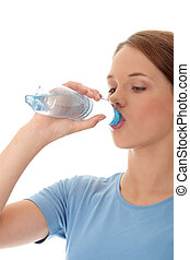 Teen woman drinking water isolated on white background