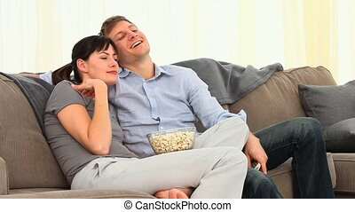 Young couple watching tv on their sofa