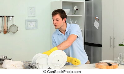 Young man washing dishes