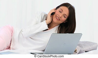Brunette woman speaking on the phone isolated on a white...