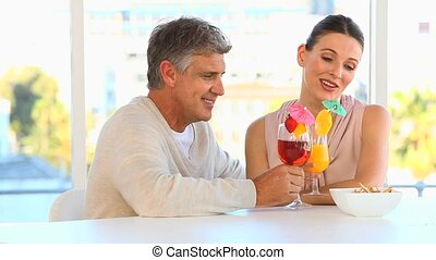 Middle aged couple drinking cocktails in the kitchen