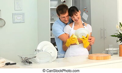 Couple washing dishes in the kitchen