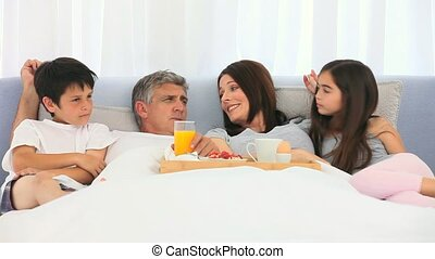 A family having breakfast on the bed