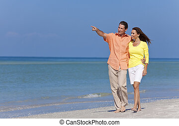 Happy Couple Walking and Pointing on A Beach - Happy man and...
