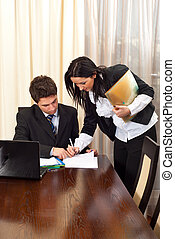 Business woman signing an agreement for other business man...