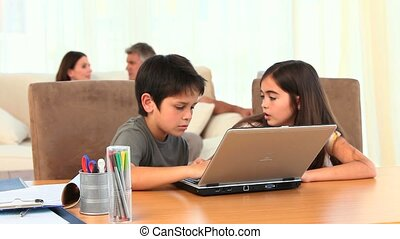 Chlidren playing on a laptop with their parents in the...