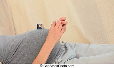 Pregnant lady playing with building blocks at home