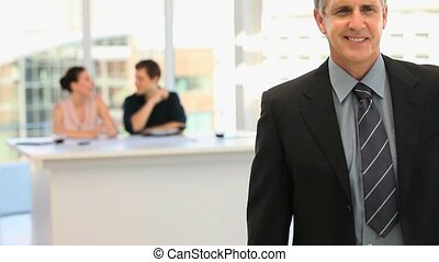 Mature businessman in suit with people in the background