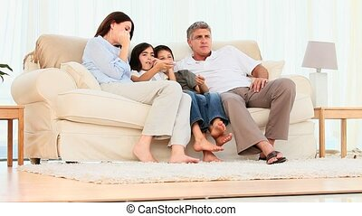 Family watching tv on a couch