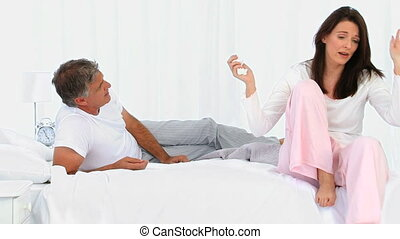 Mature couple having an argument on a bed