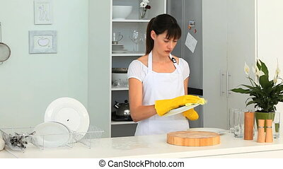 Dark-haired woman doing the dishes in the kitchen