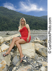 Riverbed - Young girl on a stone. Dry riverbed