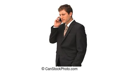 Young businessman in suit speaking on the phone against a...