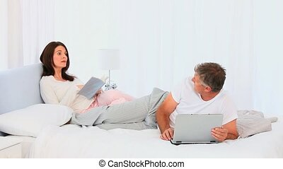 Elderly couple with book and laptop in their bedroom