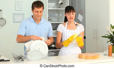Cute couple washing up together in the kitchen
