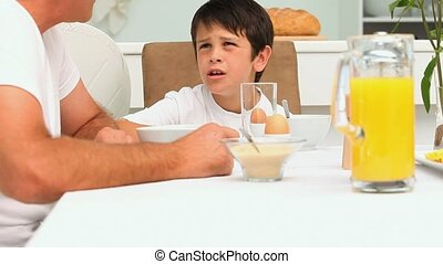 A son talking with his father during the breakfast