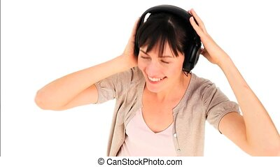 Cute brunette girl listening to music against a white...