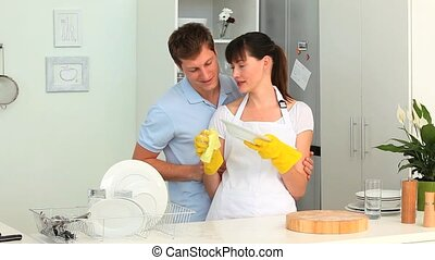 Couple washing up together in the kitchen