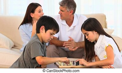 Parents looking at their children playing chess in the...