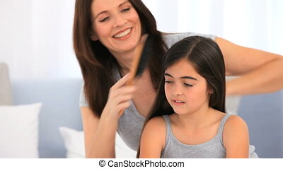 Brunette mother fixing hair of her daughter in the living...