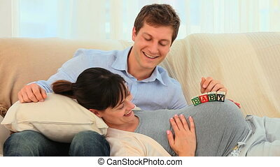 Couple playing with building blocks on their couch