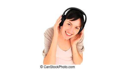 Happy woman dancing with headphones isolated on a white...