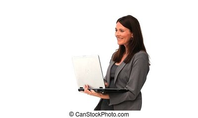 Brunette businesswoman holding with a laptop against a white...