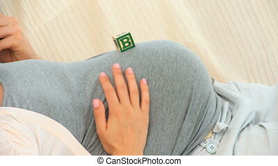 Couple playing with building blocks on a pregnant belly