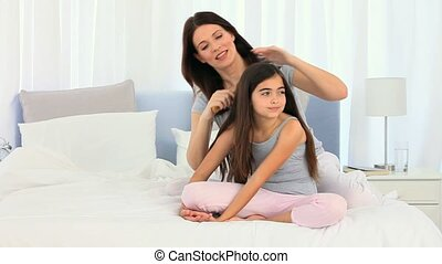 Mother fixing daughter's hair in the bedroom