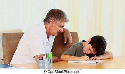 Father looking at his son doing his homework