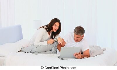 Middle aged couple looking at a laptop on their bed