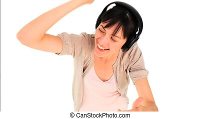 Brunette girl listening to music isolated on a white...