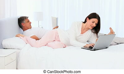 Woman showing her husband something on her laptop on the bed