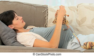 Pregnant woman knitting on her couch