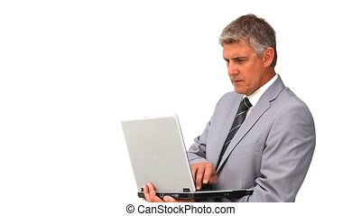 Middle aged man in suit standing with a laptop isolated on a...